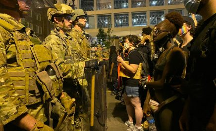 A row of police in camouflaged riot gear stand across from a line of protesters holding signs.