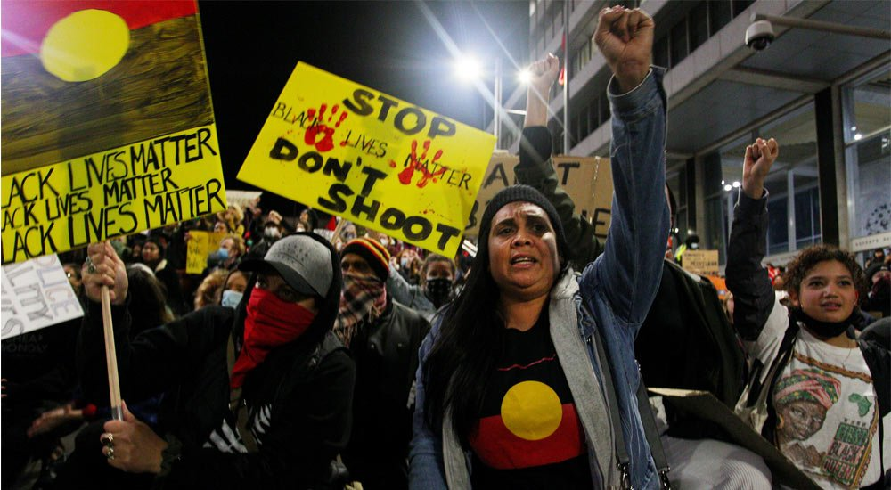 Protestors chant and bend down on their knees. They hold handmade red, yellow and black signs saying 'stop don't shoot' and Black Lives Matter. Woman in front raises her fist and is wearing an Aboriginal flag tshirt.
