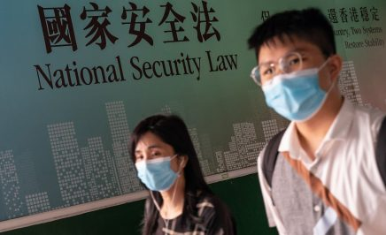 Two people wearing masks walk past a sign that reads