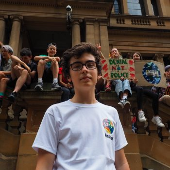 A portrait of School Strike for Climate actvist Ambrose Hayes, with other strikers sitting behind him.