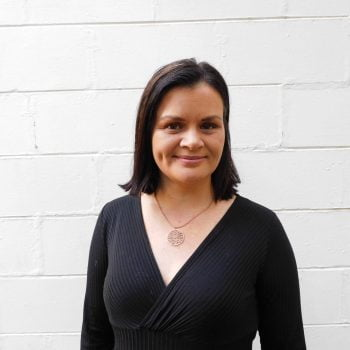 Portrait of Indigenous woman and activist Bianca Hunt. She stands in front of a white brick wall, smiling. She's wearing a black dress and pendant necklace.