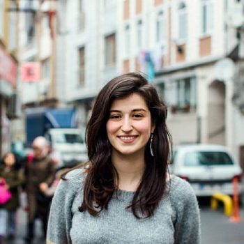 A portrait of Refugee Activist Samah Shda, smiling in the street.