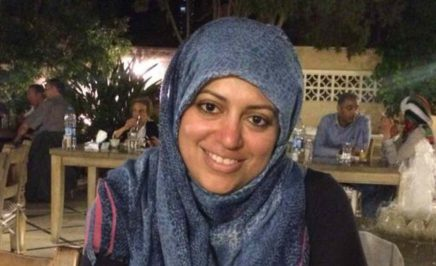 Nassima in a blue headscarf sits in a cafe.