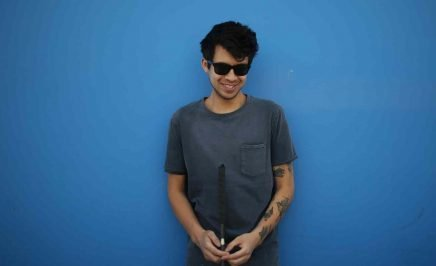 Gustavo stands with a can and dark sunglasses in a grey shirt before a blue background.