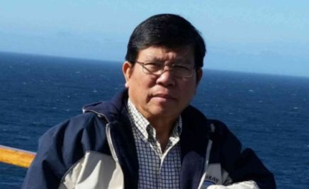 Mr Chau wears a jacket and glasses, and stands in front of the ocean.
