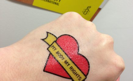 A hand with a love heart tattoo and the words
