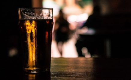 A pint of beer sitting on a wooden bench in a dark-lit room