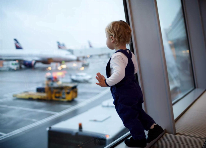 a small child leans on an airport window looking out at planes on the tarmac