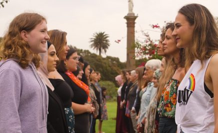 Women and girls gather in 2 lines in a park.