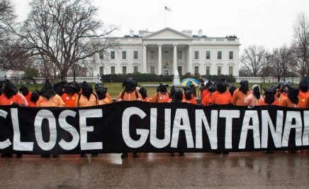 40 people standing in front of the US White House wearing orange jumpsuits holding a black sign with white writing - Close Guantanamo
