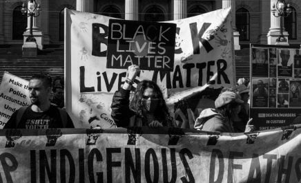 A group of protestors waving Black Lives Matter banners at the Black Deaths in Custody Rally in Melbourne, 2021.