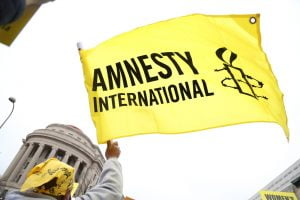Image of a yellow and black flag, featuring the Amnesty International logo, being waved.