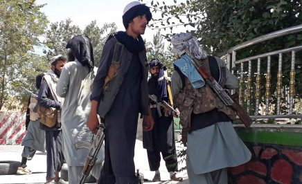 Taliban fighters armed with guns stand along the roadside in Ghazni