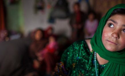 An image of a woman wearing a green hijab looks away from the camera. The background is distorted, but she is in a room with other people.