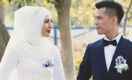 Mehray and Mirzat on their wedding day. Mehray wears a white wedding dress and hijab, Mirzat wears a black blazer. They are looking at each other.