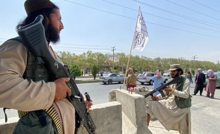 Taliban fighters stand guard at an entrance gate.