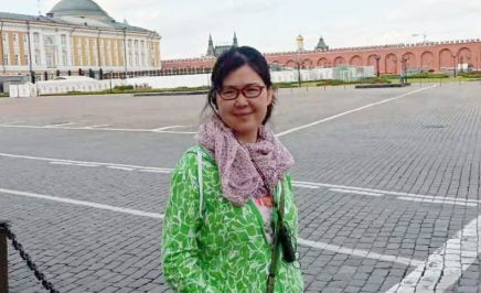 image of women wearing green top smiling into the camera looks like she is travelling abroad