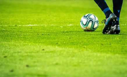 Stock image of a feet level shot of footballer kicking a ball on a pitch
