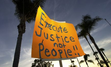 A protester holds a sign up against a backdrop of palm trees which reads 'execute justice not people' during an anti-death penalty protest.